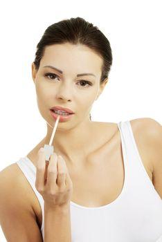 Woman putting on lip gloss
