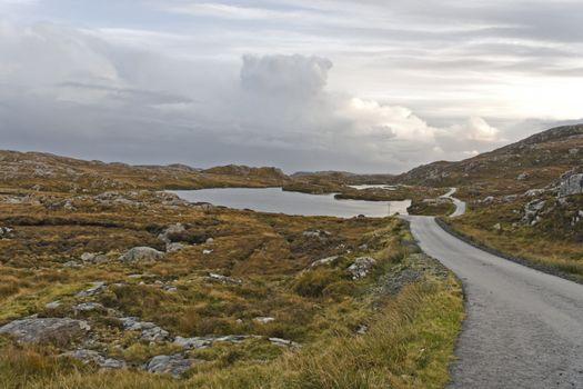 single track road on scottish isle. heathlands and loch