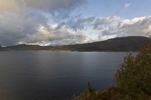 lake in the highlands with clouds and mountains