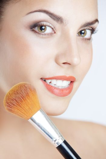 Smiling lady with makeup brush on a studio background