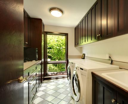 Laundry room with wood cabinets and white washer and dryer.