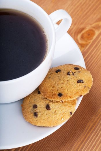 Cup of coffee with cookies on a wooden table