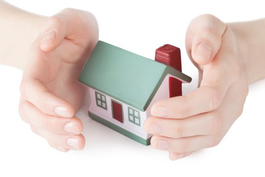 Little house toy covered by hands isolated over white background