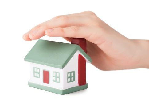 Little house toy covered by hand isolated over white background