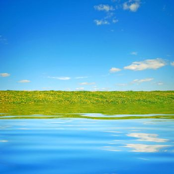Beautiful landscape. Clear water, fresh meadow and blue sky