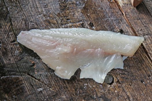 A fillet from a freshly cleaned Largemouth Bass sitting on an outdoor cleaning board.
