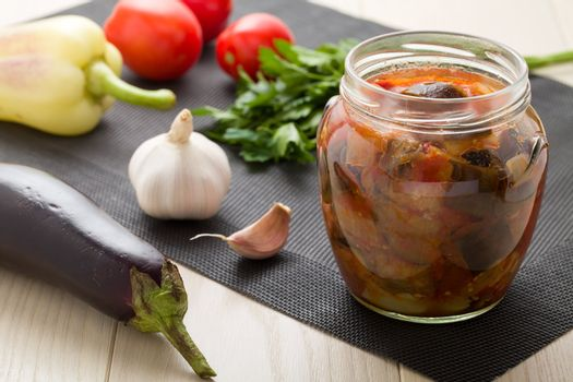 Cooked stewed eggplants in jar for canning with raw vegetables:  garlic, parsley, tomatoes, pepper on wooden table