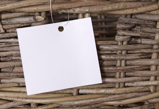 A wicker basket with a white label attached to it.