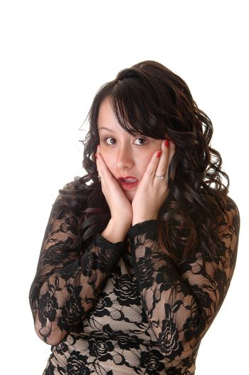 A really scared young woman holding her face in her hands, with long black curly hair in a black lace dress for white background.
