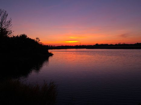 Beautiful dramatic sunset over a small countryside rural lake