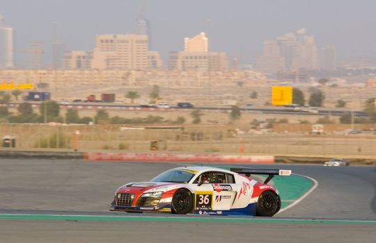 DUBAI - JANUARY 14: Car 36, an Audi R8 GT3 LMS with Dubai City in the background, during the 2012 Dunlop 24 Hour Race at Dubai Autodrome on January 14, 2012.