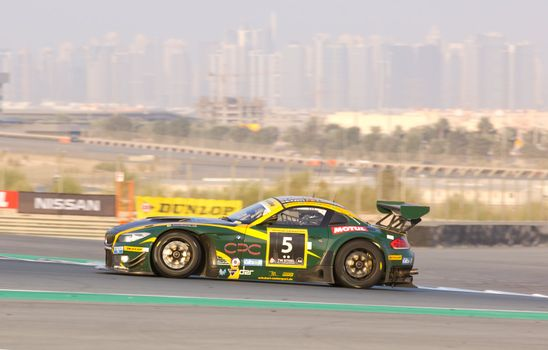 DUBAI - JANUARY 14: Car 5, a BMW Z4 GT3 with Dubai City in the background, during the 2012 Dunlop 24 Hour Race at Dubai Autodrome on January 14, 2012.