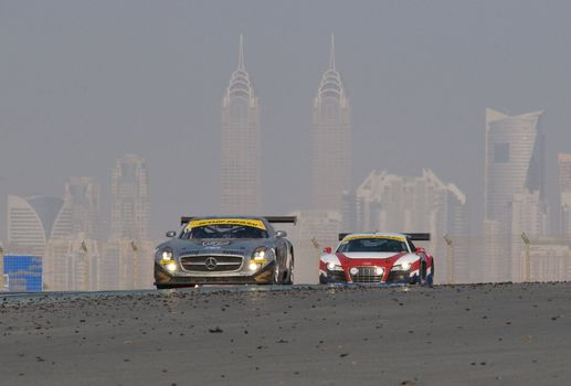 DUBAI - JANUARY 14: Mercedes SLS and Audi R8 with Dubai City in the background, during the 2012 Dunlop 24 Hour Race at Dubai Autodrome on January 14, 2012.