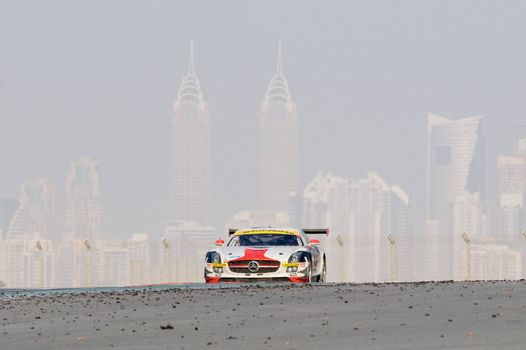 DUBAI - JANUARY 14: Car 6, a Mercedes SLS AMG GT3 with Dubai City in the background, during the 2012 Dunlop 24 Hour Race at Dubai Autodrome on January 14, 2012.