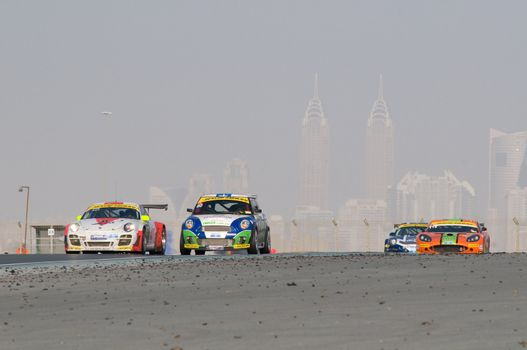 DUBAI - JANUARY 14: Porsche 997, BMW MIni and Ginetta G50 with Dubai City in the background, during the 2012 Dunlop 24 Hour Race at Dubai Autodrome on January 14, 2012.