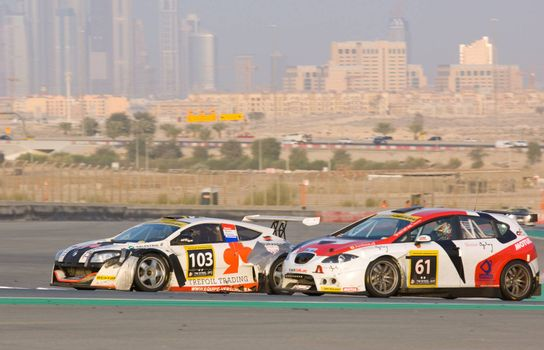 DUBAI - JANUARY 14: Renault Megane Trophy and Seat Leon Supercopa with Dubai City in the background, during the 2012 Dunlop 24 Hour Race at Dubai Autodrome on January 14, 2012.
