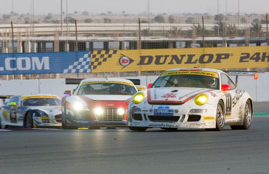 DUBAI - JANUARY 14: Porsche 997, Audi R8 and Mercedes SLS fighting for positions during the 2012 Dunlop 24 Hour Race at Dubai Autodrome on January 14, 2012.