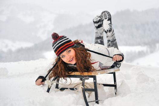 Young Beautiful Woman on sledge  in winter time