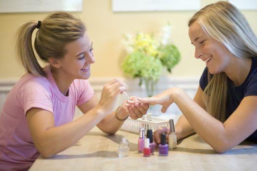 Teenage girls putting on nail polish