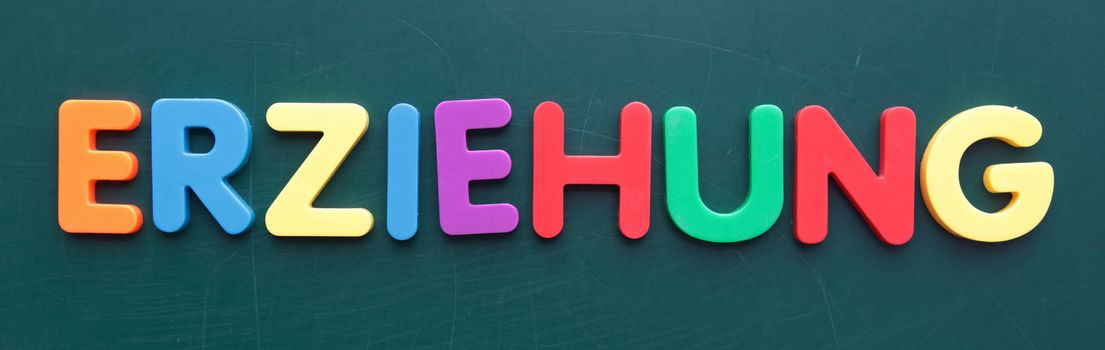 The german term child education in colorful letters on a blackboard.