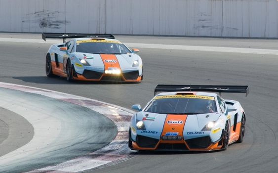 DUBAI - JANUARY 13: Two Lamborghini Gallardo LP600 in Gulf livery coming through curve 1 during the 2012 Dunlop 24 Hour Race at Dubai Autodrome on January 13, 2012.