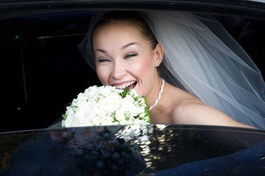 bride laugh in the wedding car
