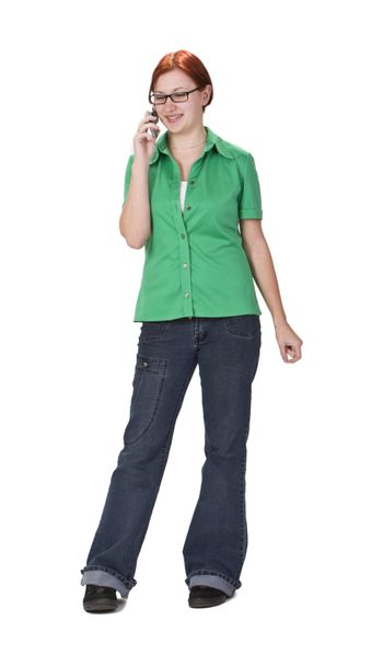 Smiling redheaded girl using a mobile phone while is standing up.