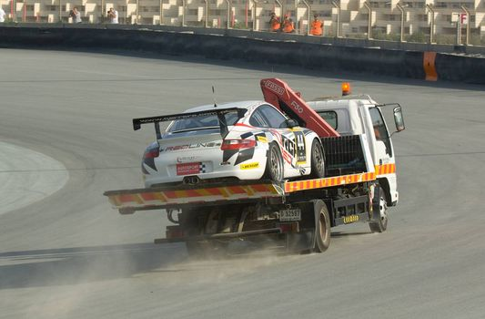 DUBAI - JANUARY 13: Car 44, a Porsche 997 GT3 Cup, being transported back to the pit after a breakdown during the 2012 Dunlop 24 Hour Race at Dubai Autodrome on January 13, 2012.