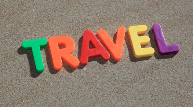 The term travel writtin in colorful letters on the sand.
