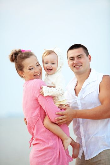 Portrait ofl young happy parents with child at the beach