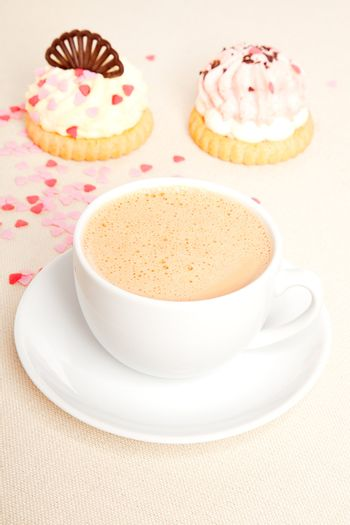 cup coffee with cake on tablecloth