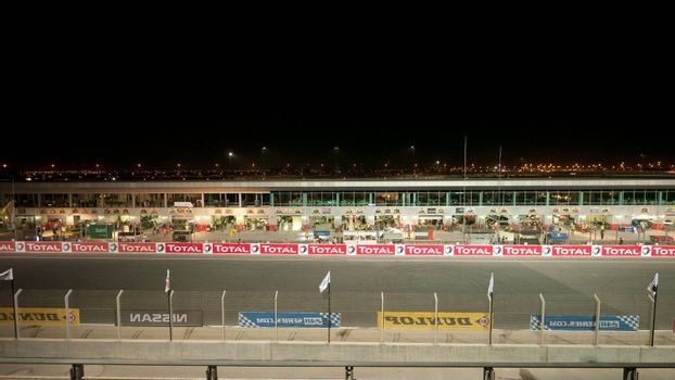 DUBAI - JANUARY 13: Start-finish straight and pit lane of the track with city lights in the background during the 2012 Dunlop 24 Hour Race at Dubai Autodrome on January 13, 2012.