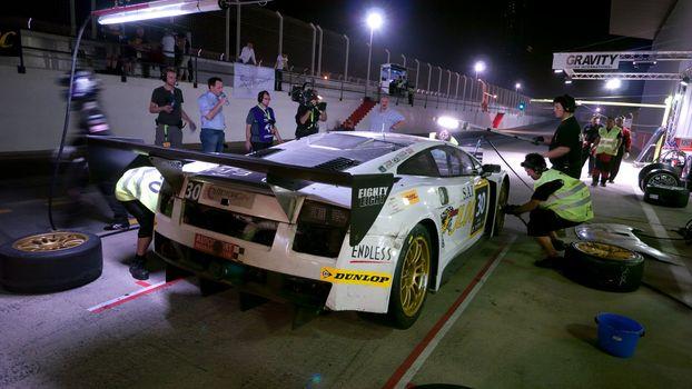 DUBAI - JANUARY 13: Car 30, a Lamborghini Gallardo LP600 during pit stop at night during the 2012 Dunlop 24 Hour Race at Dubai Autodrome on January 13, 2012.