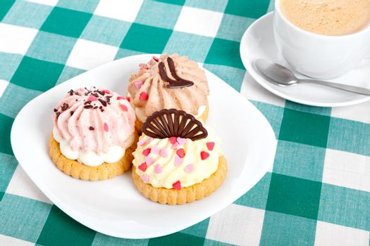 three cake on tablecloth. Coffee cup