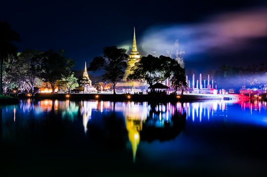 Buddhist colorful temple at night with lake reflection