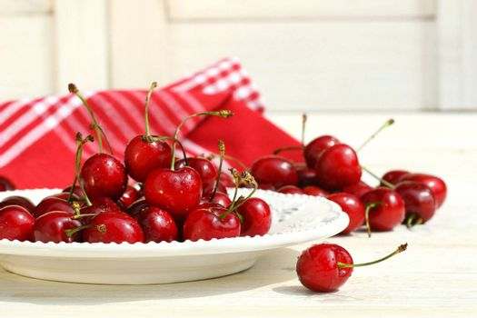 Red cherries on a plate with white shutters