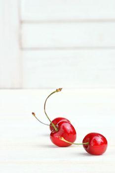 Three little cherries on white background
