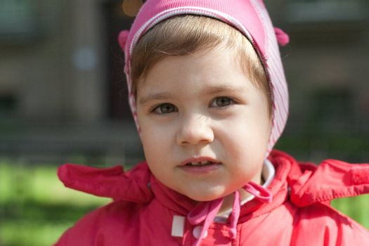 little girl in a red jacket, on the street
