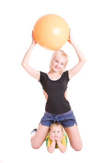 smiling happy young mother and her little son with a fitness ball on the floor