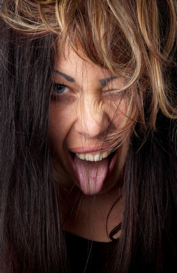 Portrait of young excited female with her tongue out and winking at camera