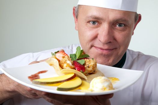 Close-up of chef holding plate with fruit dessert with ice cream, looking at camera