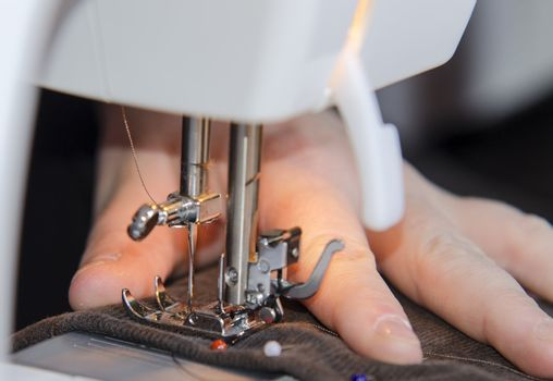Woman hands sewing on the stitching machine.