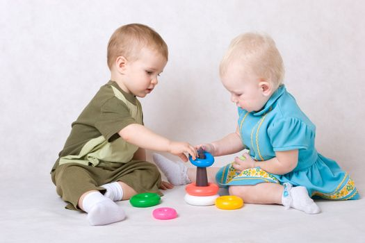 a boy and a girl of one and a half years old play pyramid on the