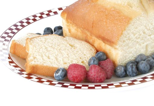 Pound cake slices with fresh fruit on a plate and shot on a white background.