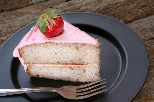 Strawberry cake with strawberry icing and garnished with a fresh strawberry.