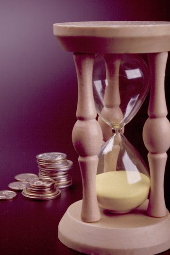 sand clock and coins
