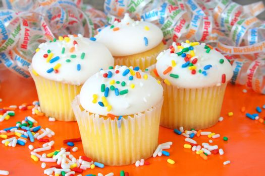 Cupcakes with sprinkles sitting on an orange background.
