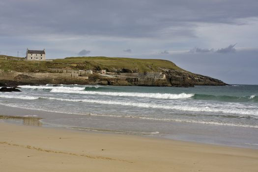 sandy coast with waves and single house in scotland