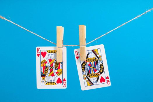 King and Queen of Hearts isolated with clothes peg rope over blue background