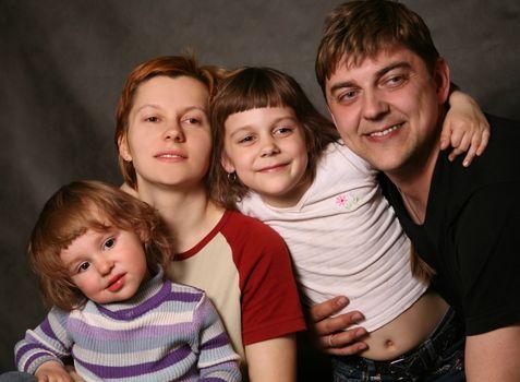 Family portrait on a dark background in studio